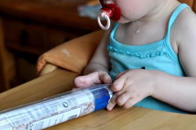Das Kind sitzt am Esstisch mit Nuckel und wartet auf das Essen