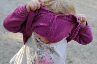 Das Kleinkind versucht seine Strickjacke selber auszuziehen
