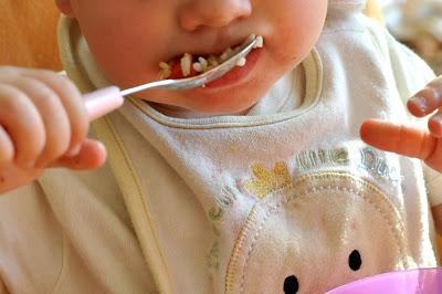 Das Kind ist mit einem Löffel ein Reisgericht