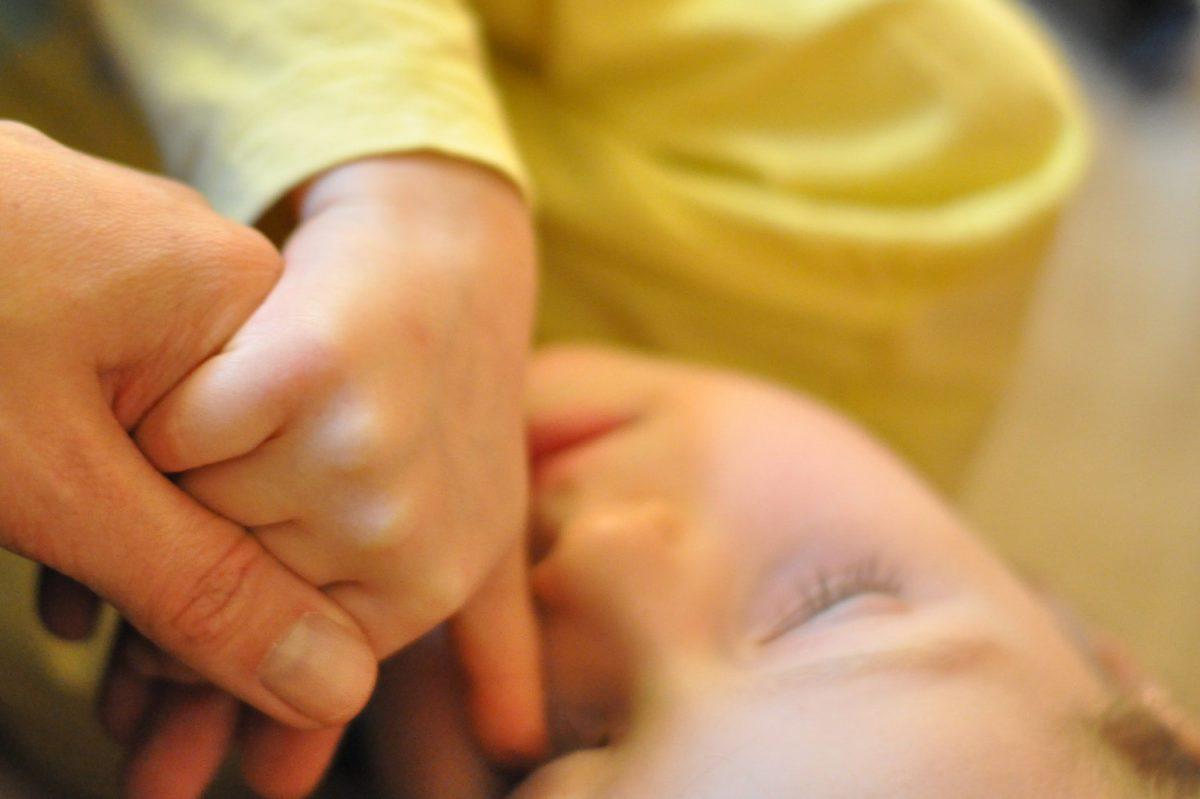 schlafendes Kind hält Mamas Hand